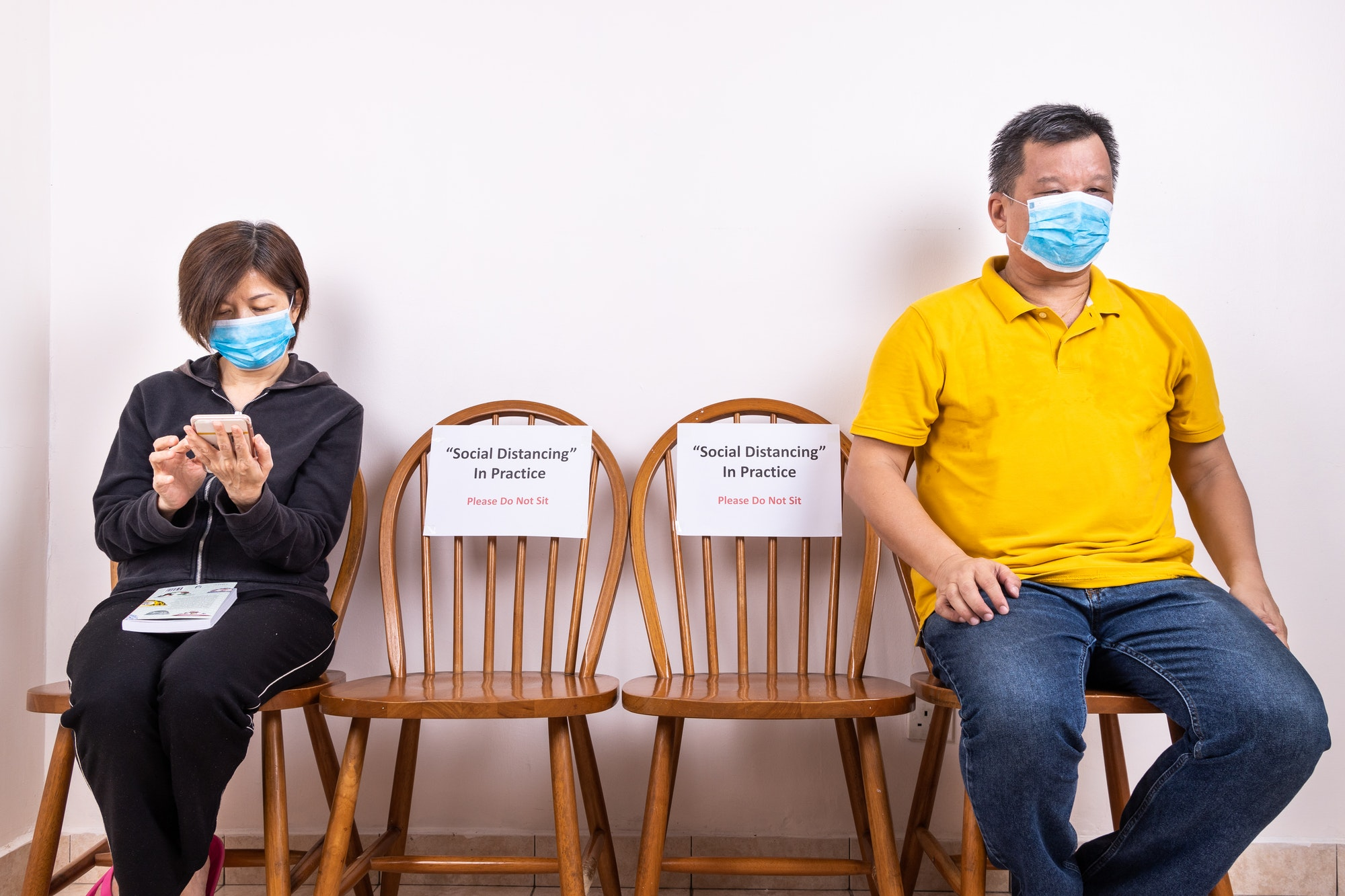 People with face mask seated in-between two chairs with Social Distancing, Do Not Sit signage.