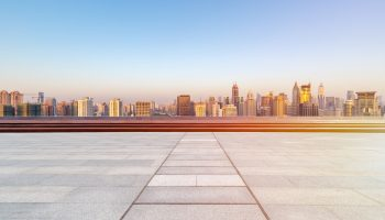 empty floor with skyline and buildings in sunrise